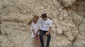 téma : Happy couple sitting on a rock, looking at each other. Man and woman in white shirts spend time outdoors in quiet private place. Top view, shooting from drone Dostupné videozáznamy