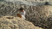 時代遅れの : Top view of young chatting couple walking along a rocky ocean coast with big waves, creating foam. Slow motion