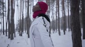 diffondere : African american girl spinning around looking up in winter forest. Beautiful girl in warm jacket spread her arms to the side, she admires the snow. Snow falls on womans face Filmati Stock