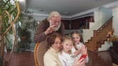 vnouče : Mature couple with their grandkids talking by cell phone using camera. Woman sitting in rolling chair. Old man and girls waving hands. Leisure of senior family and their granddaughters Dostupné videozáznamy