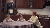 checker : Granny and two lovely granddaughters sitting in large kitcken at the table eatting soup. Happy family have lunch at home. Senior woman feeding little kids Stock Footage