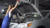 başlık : Female young auto specialist opening the hood of the car for repairing or making inspection in car service. Car service, repair, maintenance and people concept - mechanic woman working at workshop.