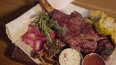 well done : Close up grilled meat with rib bone lying on pita with red cabbage, corn, mushrooms, carrot and sauces close up. Serving food in restaurant. Stock Footage