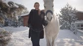 étrier : Pretty young woman walks with a beautiful white horse leading her holding a stirrup over a snow-covered country ranch.