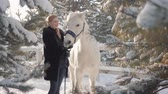 породистый : Smilling adorable blonde strokes and feeds her hands a beautiful white horse on a snowy country ranch. Concept of horse breeding.