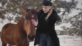 породистый : Young blond woman petting face of beautiful brown horse at a ranch. Lady hugging and kissing animal. Girl in warm clothing spends time with horse in the winter paddock