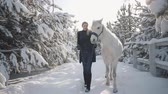 leading : Beautiful girl walks with horse in the snow winter ranch. Young woman leading her horse with his head collar talking to animal and smiling. Concept of horse breeding