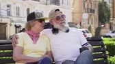 großeltern : Portrait of joyful stylish old people relaxing on the bench in the city Stock Footage
