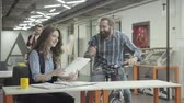 co işçi : Pretty woman and handsome bearded man communicate in the office, laughing. Beardie emotionally discussing information with a lady, holding his bike. Colleagues smiling and positive. Workplace.