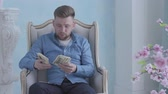 koszty : Happy rich bearded man in blue shirt sitting in the white armchair in the light room counting money. Young businessman with dollars in hands. Camera moving left