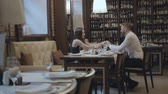 flirten : Glamour brunette woman and a handsome bearded blond man sitting at the table in front of each other. The man telling good words to his girlfriend then kisses her hand. The cute couple has a date Stockvideo
