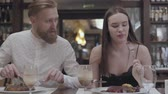 rôti de porc : Portrait of a young cute brunette woman and bearded man having supper or dinner in a restaurant or cafe.