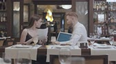 サービング : Young beautiful woman sit with papers on the table in restaurant with a mature bearded man who show her information on the laptop. Business dinner.