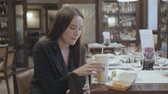 potato dishes : Pretty woman in the suit sitting in the restaurant eating fast food. Attractive brunette lady drinking cola and eating potato from paper dishes. Unhealthy lifestyle Stock Footage