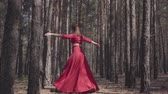 expressando : Skill young woman in red dress dancing in the forest landscape. Beautiful dancer showing classic ballet poses. Concept of female tenderness and harmony life. Contemporary dancer practicing outdoors.