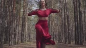 expressando : Professional graceful young woman in red dress dancing in the forest landscape. Dancer showing classic ballet poses and jumping high into the air. Concept of female tenderness and harmony life