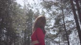 スペクタクル : Graceful womans body in red dress in the forest. Lady raises hand in the sky 動画素材