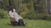 annaffiatoio : Portrait cute mature lady sitting on the lawn in the rocking chair enjoying sun. Adult grandson coming with the watering can, the woman asking him to water the bush. The man helping granny with a garden