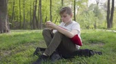 mela : Young boy sit with pillow in the green park and eating an apple. Outdoor recreation.