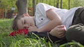 pensamento : Portrait of a cute boy lying on green grass in spring park. Outdoor recreation.