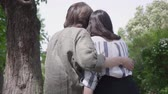 amoroso : Portrait of a young happy couple in casual clothes spending time together in the park, having a date. Lovers sitting on the bench, girl hugging her boyfriend. Leisure outdoors. Back view Stock Footage