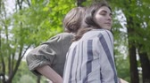 amoroso : Portrait of a young cute couple in casual clothes spending time together in the park, having a date. Lovers sitting on the bench, girl hugging her boyfriend. Leisure outdoors. Back view