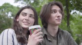 expressif : Young happy couple in casual clothes spending time together in the park, having a date. The girl drinking coffee, looking at the side. Students chatting outdoors Vidéos Libres De Droits