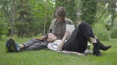 dergi : Young couple in casual clothes spending time together outdoors, having date. The guy sitting on the blanket on the grass, pretty girl lying on his laps reading magazine. Summertime leisure