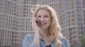 city dweller : Close-up portrait of cute smiling confident blond woman talking by cellphone in front of skyscraper. Urban lifestyle. Female city dweller with high building on background Stock Footage