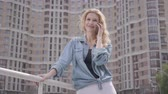 city dweller : Confident smiling blond woman in jeans jacket talking by cellphone in front of skyscraper. Urban lifestyle. Female city dweller with high building on background