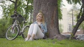 dergi : Pretty smiling woman sitting under an old tree in the park reading a journal. The modern bicycle standing near. Leisure outdoors, connection with nature Stok Video