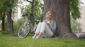 dergi : Portrait cute smiling woman sitting under an old tree in the park reading a journal. The modern bicycle standing near. Leisure outdoors, connection with nature