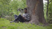 dergi : Handsome African American man sitting near his bicycle under an old tree in the park reading a book. Leisure outdoors, connection with nature. Romantic introvert spending time alone out of city Stok Video