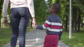 afrikai etnikai : Back view of unrecognizable African American woman walking in the park with her little son, holding hands. Cute child spending time outdoors with his mother. Loving family, carefree childhood Stock mozgókép