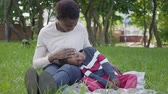 speelgoedauto : Portrait attractive African American woman sitting on the blanket with her little son playing with a toy in the park. The young mother spending time with her child outdoors. Loving family on the picnic Stockvideo