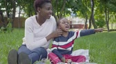 speelgoedauto : Attractive African American woman sitting on the blanket with her little son playing with a toy in the park. The young mother spending time with her child outdoors. Loving family on the picnic Stockvideo