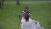 descida : Positive African American woman spreads her arms for hugs, the boy runs and hugs his mom, both fall on the blanket on the grass. Loving family resting outdoors. Camera hiding behind the tree