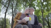 parceria : Portrait of a mature couple in love sitting on a bench in the park. Adult woman holds a beautiful bouquet of flowers while her elderly husband hugs her. Tender relationship adorable couple outdoors.