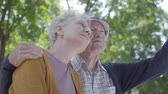 parceria : Portrait of a mature couple in love sitting on a bench in the park. Adorable woman and old man together. Tender relationship adult couple outdoors.