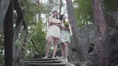 downstairs : Two young women in short dreses with flowers standing on the stairs and looking at amzing forst, trees, plants. Pretty girls walk outside the city. Cute girlfriends spending weekend together outdoors.