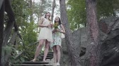 downstairs : Portrait two young women in short dreses with flowers standing on the stairs and looking at amzing forst, trees, plants. Pretty girls walk outside the city. Cute girlfriends outdoors.