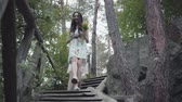 downstairs : Two young women in short dreses with flowers go down the stairs and looking at amzing forst, trees, plants. Amzing view. Stock Footage