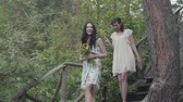downstairs : Two young women in short dreses with flowers go down the stairs and looking at amzing forst, trees, plants. Amzing view. Slow motion.