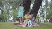 three generation : Adorable elegant senior woman sitting on the blanket under the tree in the park talking with two cute granddaughters. One girl sitting near, another standing. Happy family on the picnic.
