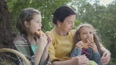 simit : Portrait adorable mature woman sitting on the grass under the tree in the park with two cute granddaughters. Grandmother breaks a bagel in half and gives to girls. Happy family spending time outdoors