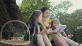 pre teen : Mature grandmother sit in the park near tree on the blanket reading a book with two granddaughters who eatting a tasty bread Stock Footage
