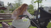 amendoins : Young happy redhead mother sitting on bench near the house with baby carriage and smiling and speaking to him on a nice spring day Stock Footage