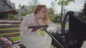 baby carriage : Adorable red-haired woman smiling looking in the pram in the park sitting on the bench. The lady enjoying the sunny day with her baby outdoors. Young mother with a child. Happy family