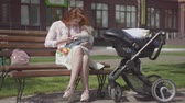 hold : Beautiful red-haired woman playing with her child sitting on the bench. The stroller standing near. The lady enjoying the sunny day with her baby outdoors. Young mother with a kid. Happy family.