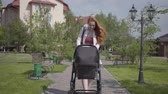 analık : Young happy redhead mother walking with baby carriage and smiling along the street on a nice spring day